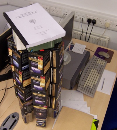 A PhD thesis on top of a big stack of empty tea boxes.